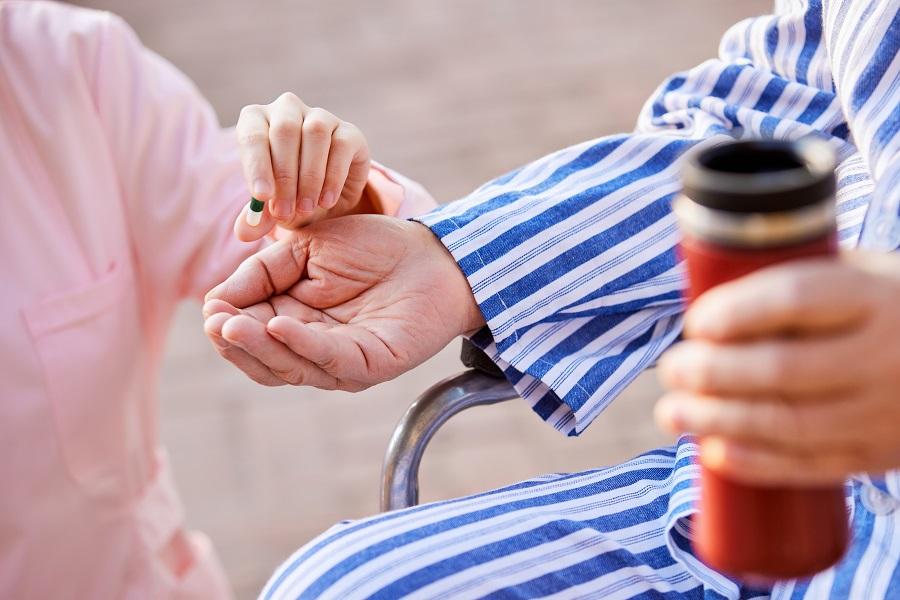 摄图网_501716676_老人在护工的照顾下吃药特写(企业商用).jpg